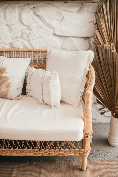 Rattan Sofa mit weißen Kissen